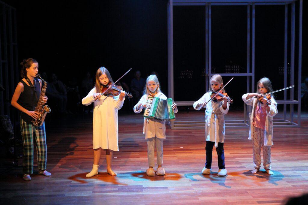 Fotografia przedstawia zespół muzyczny złożony z pięciu dziewczynek. Patrząc od prawej ku lewej stronie, są one coraz wyższe. Najstarsza, po lewej, ubrana w kraciaste spodnie i ciemną koszulkę bez rękawów, gra na saksofonie. Opiekuje się pozostałymi, dużo młodszymi od siebie, członkiniami orkiestry. Patrzy na nie z uwagą. Trzy z nich grają na skrzypcach, a czwarta, stojąca w samym środku, trzyma w rękach mały błękitny akordeon. Teatralność sytuacji podkreśla to, że poza liderką grupy pozostałe dziewczynki ubrane są w pidżamy, koszule nocne i szlafroczki. Wyglądają, jakby zostały obudzone w środku nocy lub grały przed zaśnięciem, na dobranoc. W tle po prawej stronie widać fragment konstrukcji scenografii.