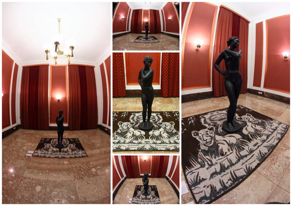 Fotografia przedstawia kolaż zdjęć ukazujących zbliżenia elementów instalacji artystycznej stworzonej ze zwykłego domowego koca i starej zamkowej rzeźby z brązu przedstawiającej stojącą nagą kobietę, która dotyka prawą dłonią swojego lewego ramienia. Rzeźba ustawiona jest na brązowym kocu z motywem lwów. Całość umieszczona jest centralnie na środku pomieszczenia. Biało-czerwona kolorystyka pomieszczenia ścian oraz symetryczny układ wszystkich elementów powodują, że instalacja ma pomnikowy charakter.