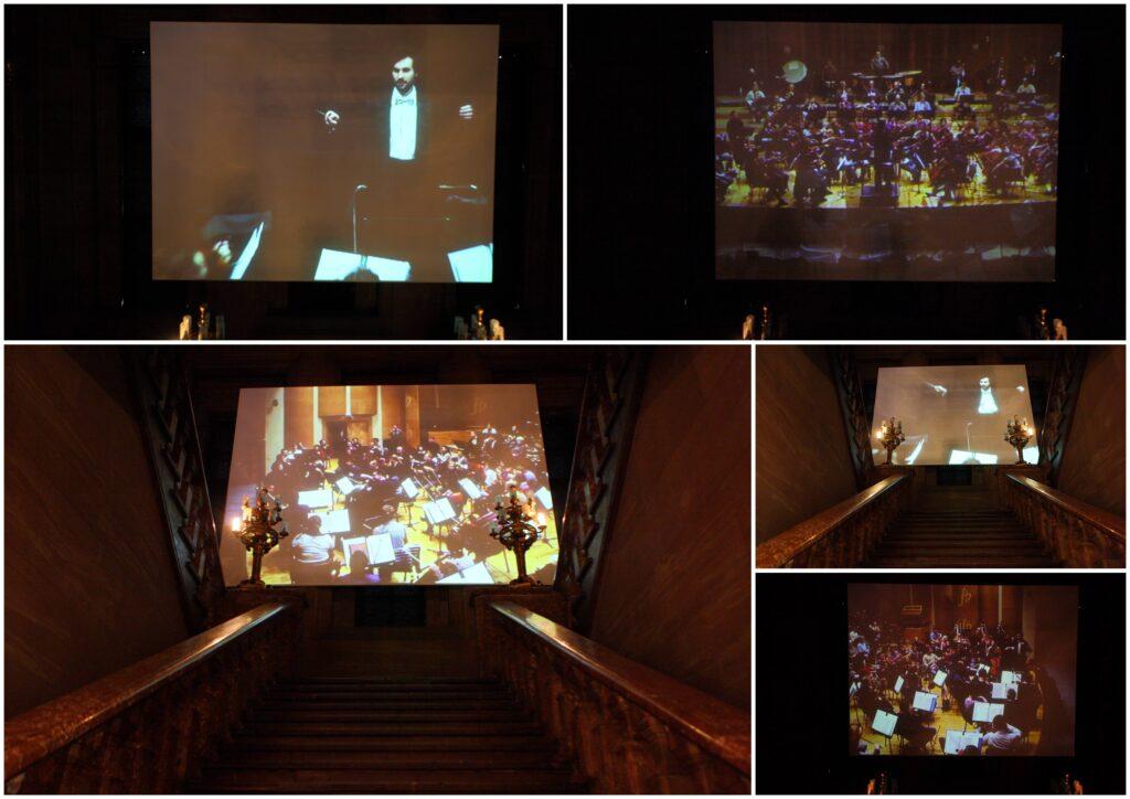 Fotografia przedstawia kolaż zdjęć w różnych ujęciach przedstawiających projekcję wideo wyświetlaną na zamkowych Schodach Paradnych wykonanych z czerwonego marmuru. Kamienne poręcze schodów wieńczą u góry dwa złote kandelabry. Sfotografowana przestrzeń jest zaciemniona i nastrojowa. U góry schodów znajduje się ogromnych rozmiarów ekran, na którym wyświetlane są zbliżenia na postać dyrygenta z uniesionymi rękami i batutą trzymaną w prawej dłoni, który dyryguje orkiestrą. Pojawiają się też ujęcia zbliżeń na grającą orkiestrę symfoniczną w filharmonii. Dyrygent ubrany jest elegancko, muzycy orkiestry znajdują się w czasie próby i mają na sobie codzienne ubrania.