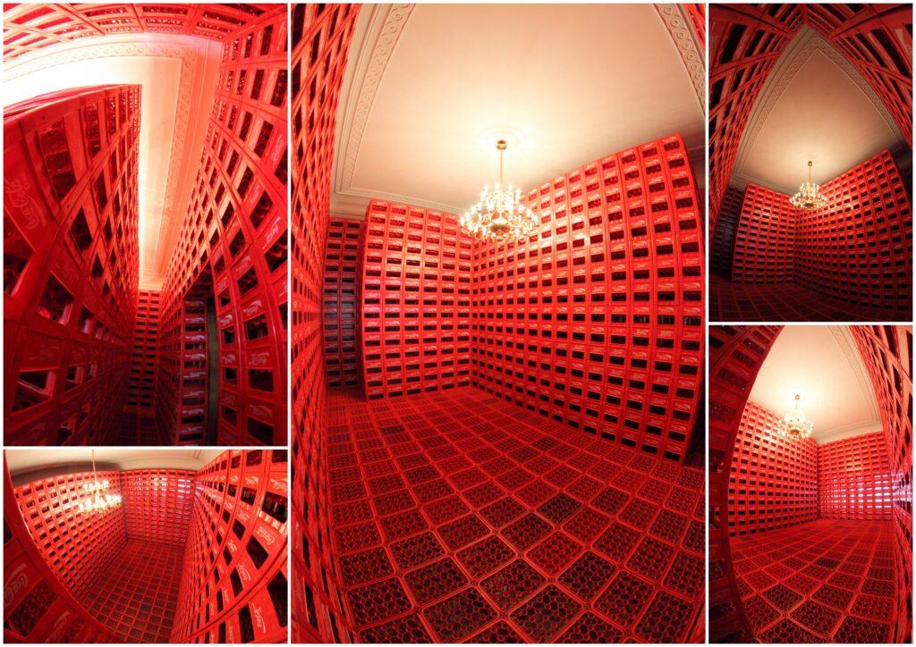 Fotografia przedstawia różne ujęcia wnętrza Pokoju Jesionowego, który w całości, zarówno podłoga jak i ściany, został zabudowany czerwonymi skrzynkami po coca-coli. Całość przypomina wnętrze zbudowane z klocków. Biały sufit ze sztukaterią i zwisający z niego wielki, rozświetlony złoty żyrandol nadają tej aranżacji zaskakujący charakter, zderzając pałacową elegancję z użytkowo-przemysłową funkcją i estetyką skrzynek.