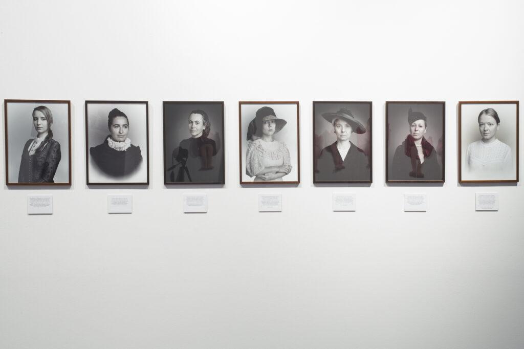 Na zdjęciu widzimy siedem czarno-białych fotografii oprawionych w ciemne, proste ramy. Każda z nich przedstawia portret kobiety. Prace powieszone są w jednym rzędzie na białej ścianie, pod nimi znajdują się białe tabliczki z opisami fotografii.