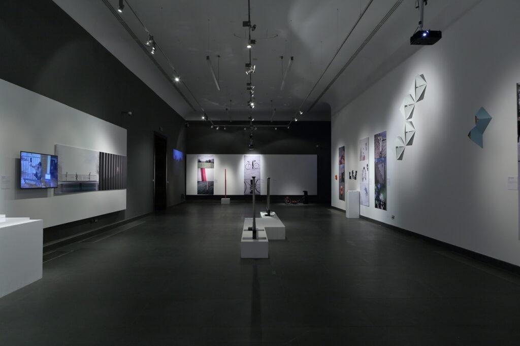 Zdjęcie przedstawia fragment aranżacji wystawy. Na białych ścianach wyeksponowane zostały prace artystów w postaci dużych, prostokątnych wydruków projektów lub zrealizowanych obiektów, np.   zamontowanych na ścianach dziupli dla ptaków. Kilka prac pokazanych zostało na białych kubikach umieszczonych na środku sali i po jej bokach. Pod sufitem widać szyny z lampami oświetlającymi przestrzeń wystawy, podwieszony projektor po prawej stronie i monitor po lewej. Podłoga sali jest grafitowa.