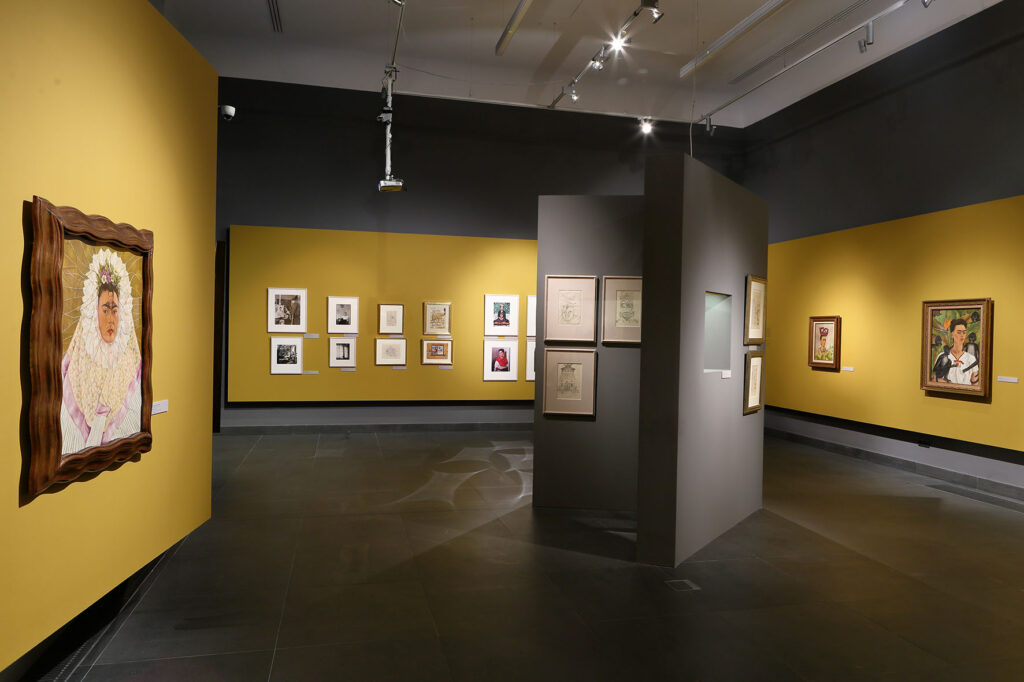 Na zdjęciu widać fragment aranżacji wystawy. Na pomalowanych na żółto ścianach powieszone są obrazy Fridy i Diego oraz fotografie. Na środku znajduje się wolnostojąca ścianka z rysunkami artystki.