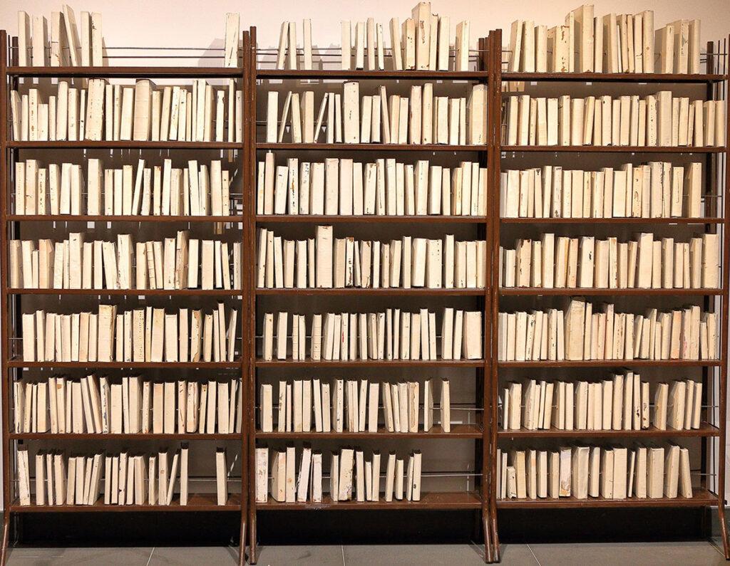 Na zdjęciu widzimy trzy brązowe, metalowe regały, które w całości wypełnione są różnymi książkami bez okładek. Wszystkie książki wyglądają podobnie, różnią się jedynie wielkością i wysokością.