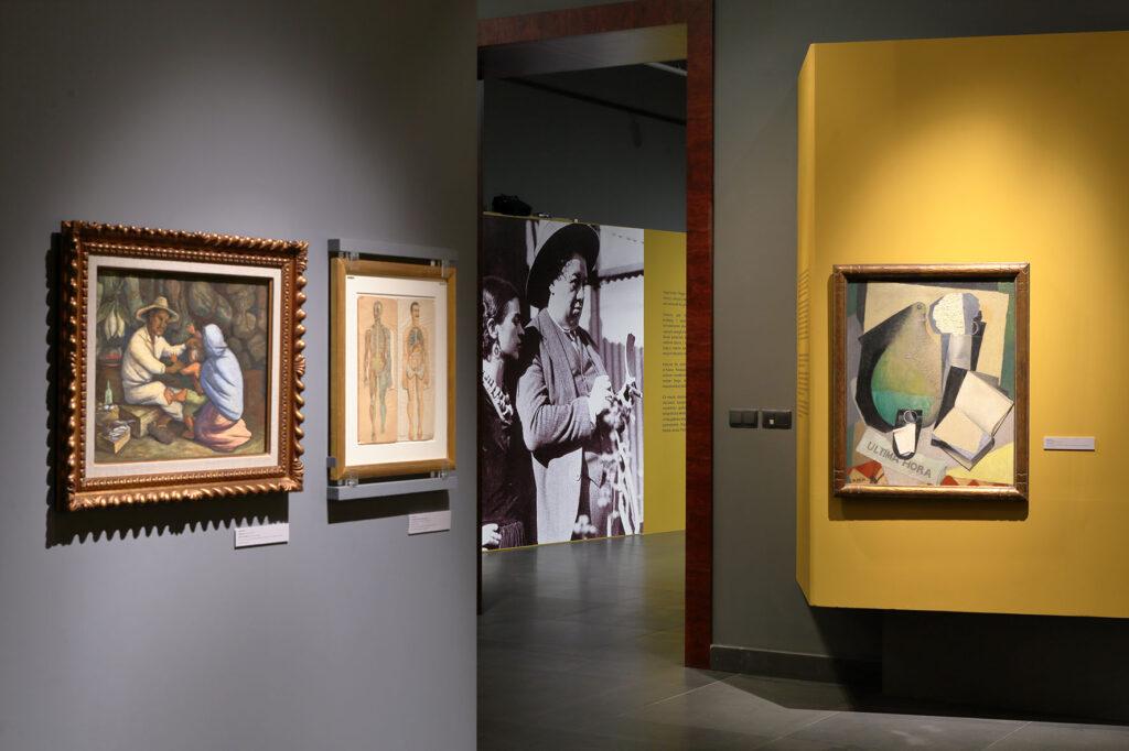 Na kolorowej fotografii widać fragment aranżacji wystawy. Na pomalowanych na żółto i szaro ścianach powieszone są obrazy Fridy i Diego. Na drugim planie znajduje się duża czarno-biała fotografia przedstawiająca parę artystów.