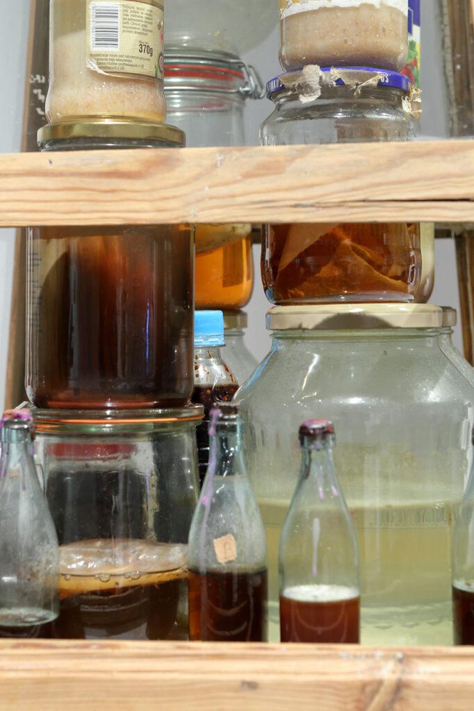 Kadr fotografii wypełniają różnej wielkości słoiki, słoiczki i butelki stojące jedne na drugich. Znajdują się w nich nieznane nam płyny, preparaty i podlegające rozkładowi części organiczne.