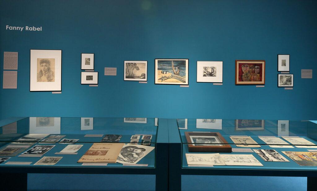 Na zdjęciu widać fragment aranżacji wystawy grafik Fanny Rabel. Na pierwszym planie są szklane gabloty, a w nich rysunki, fotografie oraz czasopisma poświęcone twórczości artystki. Na drugim planie widać powieszone na turkusowej ścianie obrazy oraz biały napis o treści: Fanny Rabel, który mieści się po lewej stronie.
