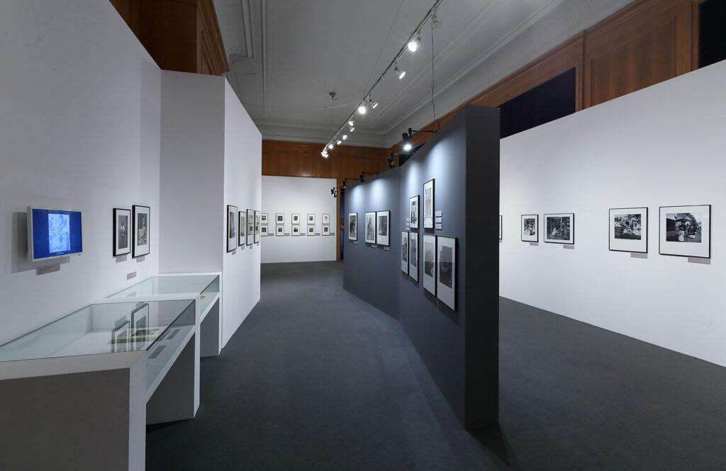 Na zdjęciu widać fragment aranżacji wystawy Bernice Kolko. W biało-szarym wnętrzu wiszą czarno-białe fotografie w ramach. Po lewej stronie znajdują się dwie szklane gabloty i mały monitor.