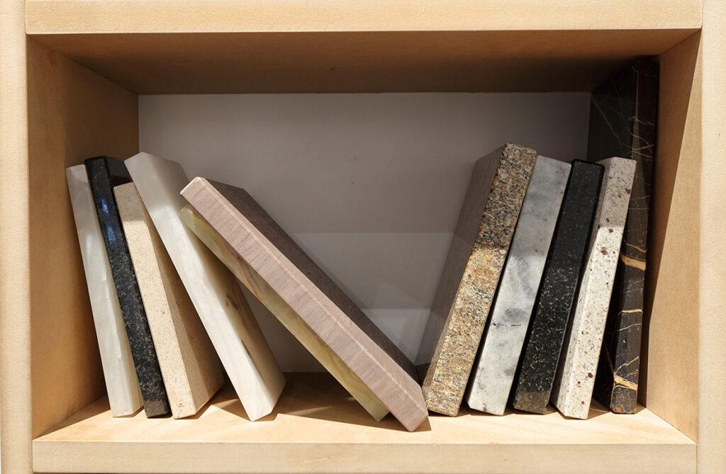 Na zdjęciu widzimy jasną, drewnianą półkę z książkami, które wykonane są z różnych gatunków marmuru.