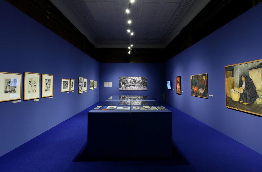 Na zdjęciu widać fragment aranżacji wystawy prac z kolekcji sztuki meksykańskiej Muzeum Narodowego w Warszawie. Po środku sali znajdują się cztery szklane gabloty wypełnione książkami i czasopismami, a na niebieskich ścianach zawieszone są prace malarskie i graficzne.