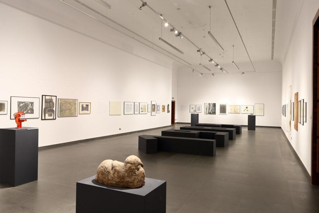 """Na zdjęciu widzimy fragment aranżacji wystawy. Na białych ścianach znajdują się rysunki i grafiki oprawione w ramy. Podłoga sali jest grafitowa. Stoją na niej cztery postumenty, dwa z przodu i dwa z tyłu, na których umieszczone zostały rzeźby. Pośrodku sali znajduje się duży, przestrzenny napis """"1989"""". Pod sufitem widać szereg lamp oświetlających prace na wystawie."""
