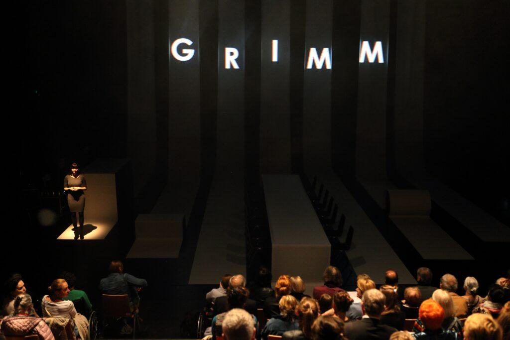 Zdjęcie zostało wykonane na chwilę przed rozpoczęciem spektaklu. Widownia jest jeszcze oświetlona. Widzimy trzy pierwsze rzędy publiczności siedzącej tyłem. Przestrzeń sceniczna jest jeszcze zaciemniona. Mimo to dość dobrze widoczna jest scenografia spektaklu zbudowana z siedmiu białych, szerokich pasów tkaniny. Zawieszone pod sufitem opadają, płynnie układając się na płaszczyźnie podłogi. Środkowy pas przykrywa dodatkowo długi stół, przy którym ustawiono symetrycznie ciemne krzesła. Jedyną postacią obecną na scenie jest kobieta stojąca po lewej stronie i ubrana w ciemną sukienkę. Wyciągnięta z mroku przez snop światła rzucony z reflektora czeka na początek przedstawienia, spokojnie wpatrując się w widownię. Dominującym elementem fotografii są duże litery wyświetlone wysoko na opadających z sufitu pasmach tkaniny. Tworzą one napis będący jednocześnie tytułem spektaklu: GRIMM.