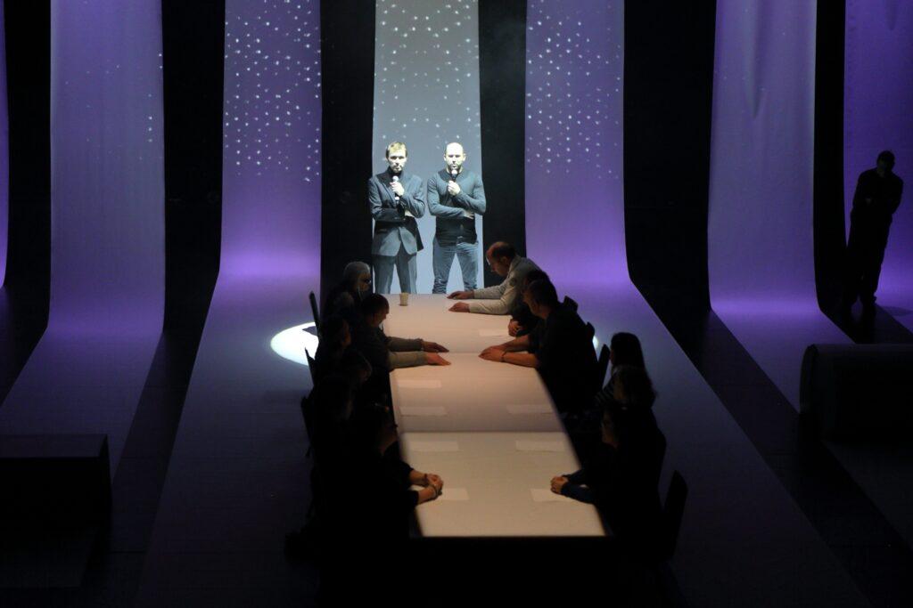 Zdjęcie przedstawia centralną część przestrzeni, w której odbywa się spektakl. Cztery pasy tworzącej scenografię tkaniny podświetlone są na fioletowo, a piąty, środkowy, na błękitno. To przed nim stoi dwóch mężczyzn trzymających przy ustach mikrofony. Mężczyzna po lewej ubrany jest w garnitur, a stojący po prawej w sweter i niebieskie dżinsy. Stoją u szczytu długiego stołu okrytego białą tkaniną. Po jego obu stronach blatu siedzą aktorzy. Ich sylwetki giną w mroku. Wyraźnie widoczne są jedynie leżące na stole ręce.
