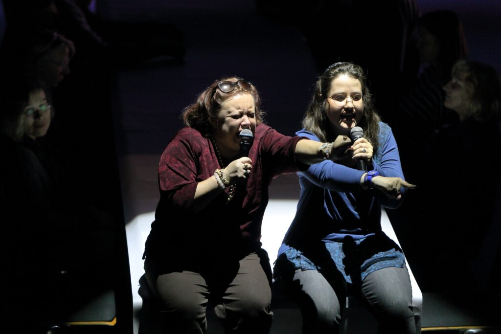 Na zdjęciu widzimy wyraźnie dwie kobiety, siedzące na skraju pokrytego białą tkaniną stołu. Ukazane są od kolan w górę. Kobieta po lewej stronie ekspresyjnie krzyczy do mikrofonu, w kierunku wskazywanym wyciągniętą do przodu lewą ręką. Jest ubrana w bordową bluzkę i ciemne spodnie. Nałożone na głowę słoneczne okulary przytrzymują jej kasztanowe, poprzetykane siwizną włosy. Druga kobieta, ubrana w niebieską bluzkę i ciemne spodnie, nie jest aż tak ekspresyjna. Wydaje się jednak wspierać przekaz koleżanki, wskazując prawą ręką w tym samym kierunku. W lewej trzyma mikrofon. Ma długie, ciemne włosy i duże, okrągłe okulary w drucianej oprawie. Po obu stronach siedzących postaci widać zarysy twarzy dwóch innych kobiet pogrążone w mroku.