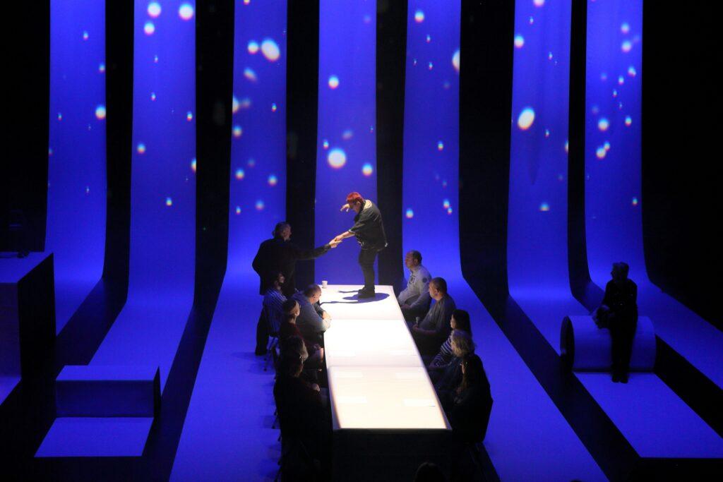 Zdjęcie w szerokiej pespektywie przedstawia całą przestrzeń, na której odgrywany jest spektakl. Siedem pasów tkaniny budującej scenografię podświetlonych jest na niebiesko. Opadając pionowo z sufitu, przechodzą płynnie w poziom i biegną dalej w kierunku widowni. Ich pionowy odcinek stanowi tło, na którym wyświetlone są białe, okrągłe plamy imitujące rozgwieżdżone niebo. W centrum fotografii znajduje się biały stół, ustawiony prostopadle. Po jego obu stronach siedzi symetrycznie dziesięcioro aktorów. Ich uwaga skierowana jest na główną postać fotografii – stojącą na stole i widzianą z boku kobietę o krótkich, rudych włosach. Pochylona do przodu prawą rękę ma uniesioną na wysokości głowy. Lewą podaje mężczyźnie ubranemu w ciemny garnitur, który stoi po lewej stronie stołu. Kompozycję zdjęcia uzupełnia ciemna sylwetka osoby siedzącej w prawym dolnym rogu, przypatrującej się całemu wydarzeniu.