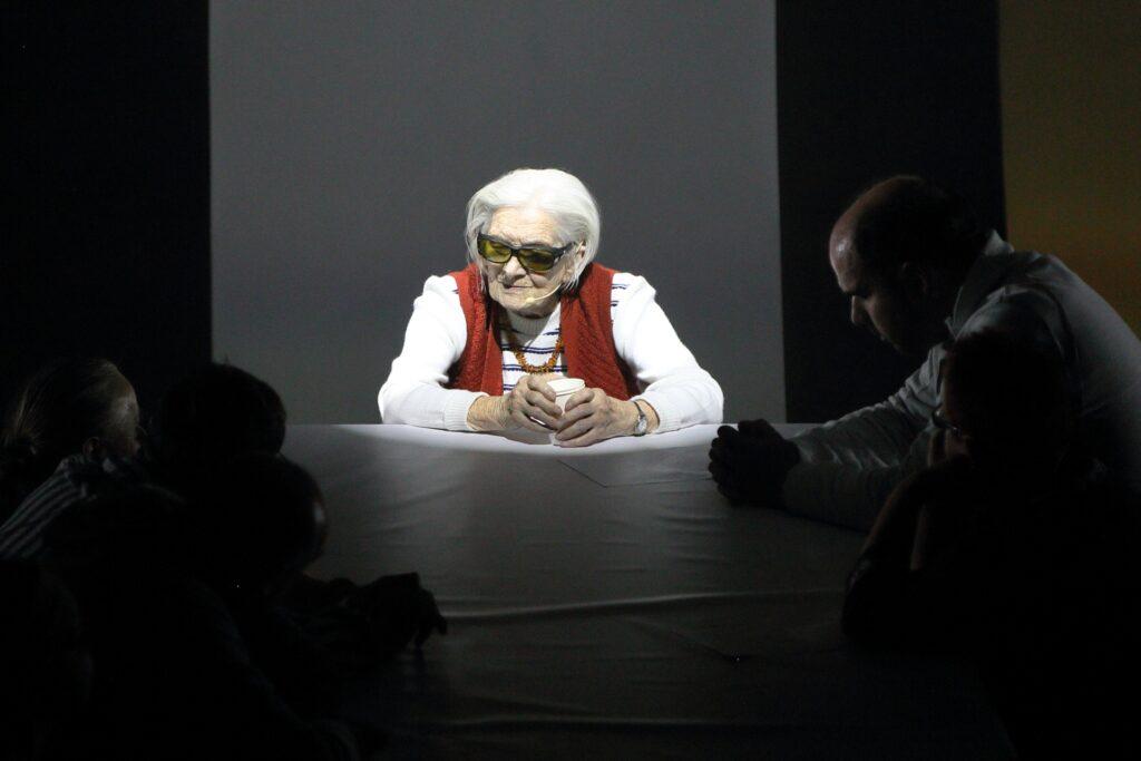 Centralną postacią fotografii jest starsza kobieta. Bardzo wyraźnie oświetlona siedzi przodem na szczycie stołu przykrytego białą tkaniną. Ma siwe, średniej długości włosy. Górną część pełnej zmarszczek twarzy przykrywają okulary w ciemnej oprawie z zieleniącymi się szkłami. Jest zamyślona. Kieruje wzrok lekko w dół, w swoją prawą stronę. Ubrana jest w biały sweterek w delikatne, poziome ciemne paski. Na niego założony ma rdzawy, wełniany bezrękawnik. W opartych o stół rękach trzyma papierowy kubek. Jej sylwetkę widzimy na szarym tle. Po obu stronach postaci jest o wiele ciemniej. Na niemal czarnym tle rysują się sylwetki kilku siedzących przy stole osób. Najwyraźniej widoczny jest profil młodego, łysiejącego mężczyzny.