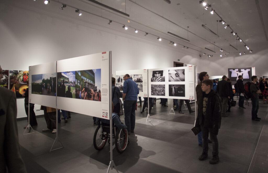Na zdjęciu widać salę wypełnioną ludźmi, którzy oglądają wystawę fotograficzną, prezentowaną w postaci dużych, kolorowych i czarno-białych plansz na metalowych, srebrnych stelażach. Podłoga Sali jest grafitowa, pod sufitem zaś widać ciąg lamp oświetlających ekspozycję.