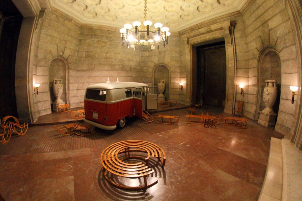 Fotografia przedstawia  wnętrze zamkowej Sieni Przejazdowej, w całości wykonanego z kamienia − ściany z szarego, a podłoga z czerwonego marmuru. Narożniki wnętrza zdobią wielkie, rzeźbione kamienne wazy ustawione w zaokrąglanych niszach. Przy jednej ze ścian ustawiony został duży, biały marmurowy tron cesarski, którego siedzisko podtrzymują dwa słonie. W tym niezwykle monumentalnym, kamiennym wnętrzu umieszczona została artystyczna instalacja. Składają się na nią stojąca pośrodku sieni stara,  prawdziwa furgonetka marki Volkswagen w kolorze czerwono-białym. Z otwartych drzwi części transportowej samochodu wydostają się drewniane sanki o przedziwnych kształtach, które porozstawiane są we wszystkich częściach pomieszczenia. Sanki są naturalnej wielkości, niektóre dziwnie powykręcane na boki bądź w kółko, inne mają płozy dopasowane do kształtów schodów lub przypominają kołyskę albo mają formę płaskiej trumienki na płozach. Całość wygląda dość zaskakująco, abstrakcyjnie i łączy w sobie zarówno humor, jak i elementy grozy.