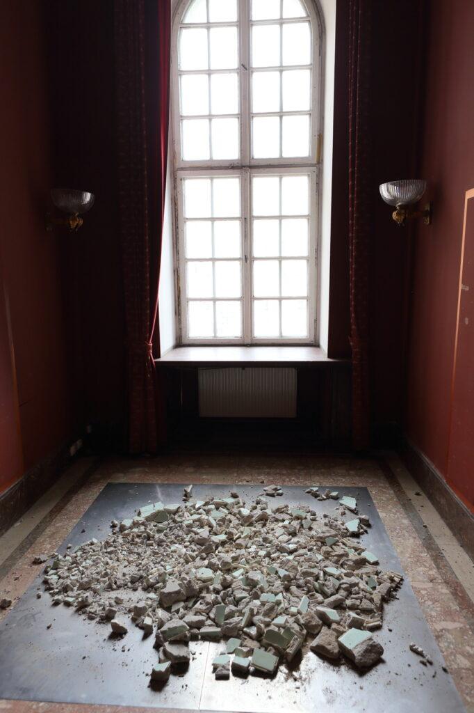 Fotografia przedstawia jedną z sal Centrum Kultury ZAMEK. Na pierwszym planie, na podłodze znajdują się symbolicznie rozsypane, zdemontowane z pływalni białe kafelki, a właściwie powstały z nich gruz. Drugi plan stanowi duże okno oraz dwa szklane, zabytkowe kinkiety. Ściany pomieszczenia pomalowane są na kolor bordowy.