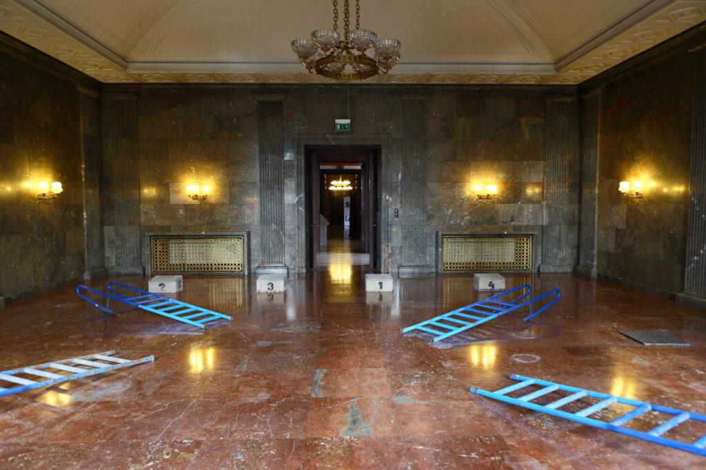 Fotografia przedstawia obecną Salę Kominkową, będącą dawniej fragmentem kaplicy Zamku Cesarskiego, zniszczonej przez nazistów i przerobionej na gabinet Adolfa Hitlera. W czterech narożnikach pomieszczenia, na marmurowej, bordowej podłodze ułożono zdemontowane, niebieskie drabinki z pływalni, które tworzą jakby krzyż. Na ścianach z szarego marmuru widzimy zapalone kinkiety oraz drzwi wejściowe pośrodku. Z białego sufitu zwisa duży, zabytkowy żyrandol.