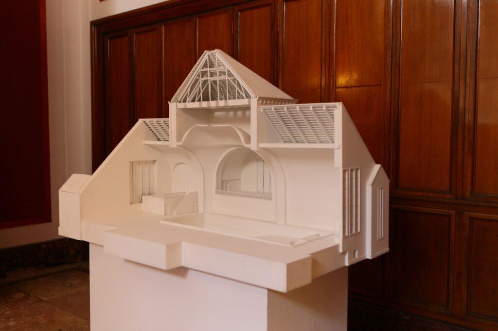 Na fotografii widzimy białą makietę synagogi, która została przebudowana na pływalnię. Makieta została postawiona na białym postumencie i znajduje się w zabytkowej, drewnianej sali Zamku.