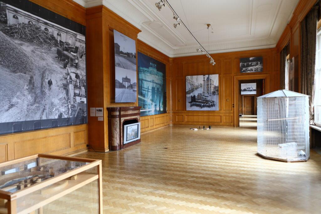 Na fotografii widzimy fragment aranżacji wystawy z kilkoma pracami. Są to, rozwieszone na zabytkowych, drewnianych ścianach: wielkoformatowe, czarno-białe fotografie, duża, metalowa klatka dla ptaków oraz fragment gabloty. Podłoga sali wyłożona jest parkietem, ściany są drewniane, a sufit biały. W tylnej części widzimy otwarte drzwi prowadzące do kolejnego pomieszczenia, zaś po lewej stronie marmurowy kominek, w otworze którego znajduje się telewizor.