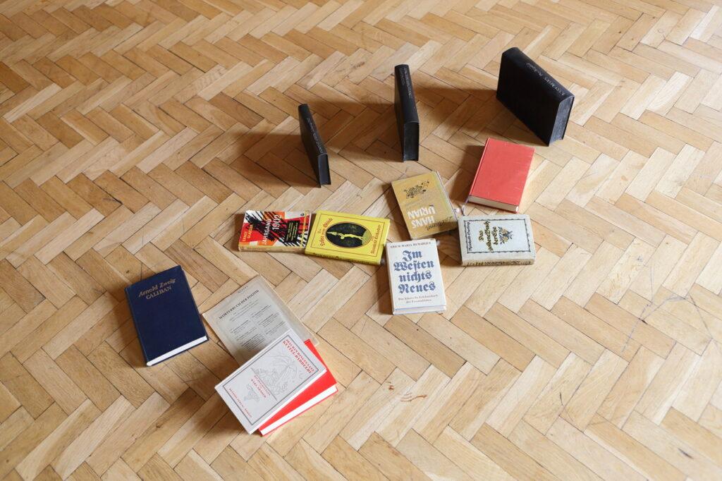 Na kolorowej fotografii widzimy drewnianą podłogę, na której położono kilka niemieckich książek.