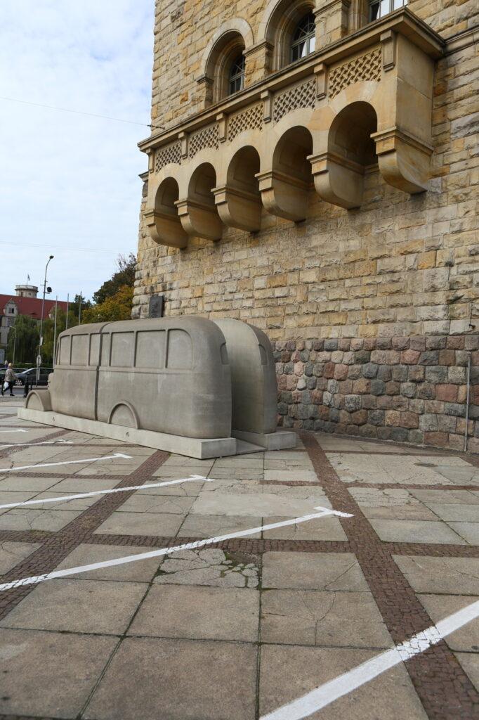 Na fotografii widzimy betonową rzeźbę szarego autobusu, stojącego na płycie parkingowej, tuż przy zamkowej wieży, pod dużym balkonem. Są to dwa szare odlewy przepołowionego pojazdu. Budynek zamku zbudowany jest z piaskowca. Z lewej strony widzimy fragment miasta oraz niebo.