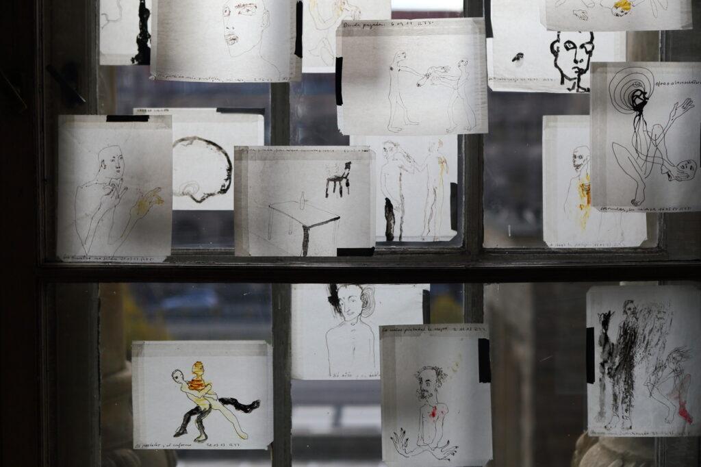 Zdjęcie przedstawia fragment starych okien, do których przyklejono białe, małe kartki papieru ze szkicowymi rysunkami różnych postaci.