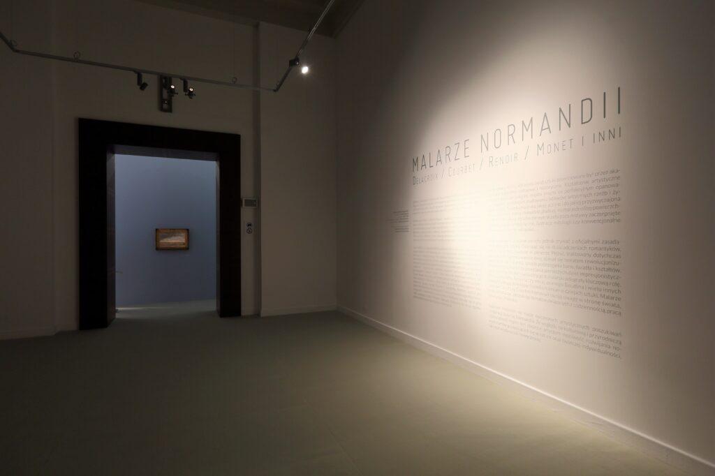 """Fotografia przedstawia przedsionek sali wystaw, będący wprowadzeniem do wystawy. Pomieszczenie jest oświetlone punktowym reflektorem wydobywającym po prawej stronie białą płaszczyznę ściany. Na jej powierzchni znajduje się wyklejony czarnymi dużymi literami tytuł wystawy """"Malarze Normandii. Delacroix, Courbet, Renoir, Monet i inni"""" i poniżej drobniejszymi literami tekst wprowadzający w temat wystawy. Na podłodze leży dywanowa wykładzina w jasnym piaskowym kolorze. W tle widać duże brązowe obramienie przejścia z przedsionek do głównej sali wystaw. Widok głównej sali wystaw przysłania błękitna ściana ustawiona w świetle przejścia, po środku którego zawieszony jest mały obraz w rzeźbionej, złoconej ramie, oświetlony delikatnym punktowym światłem."""