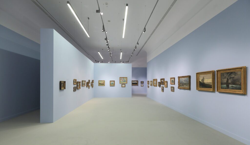 Fotografia przedstawia widok ekspozycji w głównej sali wystaw. Po lewej stronie stoi ściana działowa w kształcie odwróconej litery L. Błękitne ściany i leżąca na podłodze dywanowa wykładzina w jasnym piaskowym kolorze tworzą z jednej strony nastrój salonowego wnętrza, z drugiej przywodzą skojarzenia z morzem i plażą. Na ścianach wiszą niewielkie obrazy oprawione w rzeźbione, złocone ramy oświetlone jasnym światłem z reflektorów umieszczonych pod białym sufitem.