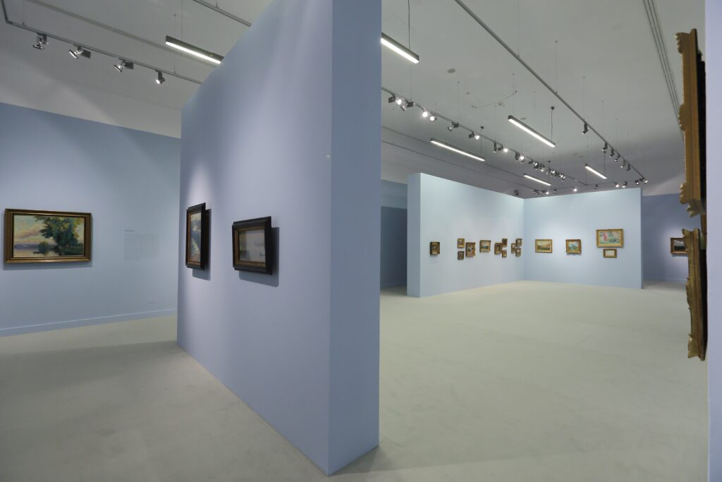 Fotografia przedstawia widok ekspozycji w głównej sali wystaw. Ujęcie wykonane jest z narożnika po przekątnej sali, ukazując niemal całą jej panoramę. Po lewej stronie znajduje się wolnostojąca ściana ekspozycyjna, po prawej, głęboko w tle, wstawiona jest ściana działowa w kształcie odwróconej litery L. Błękitne ściany i leżąca na podłodze dywanowa wykładzina w jasnym piaskowym kolorze tworzą z jednej strony nastrój salonowego wnętrza, z drugiej przywodzą skojarzenia z morzem i plażą. Na ścianach wiszą niewielkie obrazy oprawione w rzeźbione, złocone ramy oświetlone jasnym światłem z reflektorów umieszczonych pod białym sufitem.