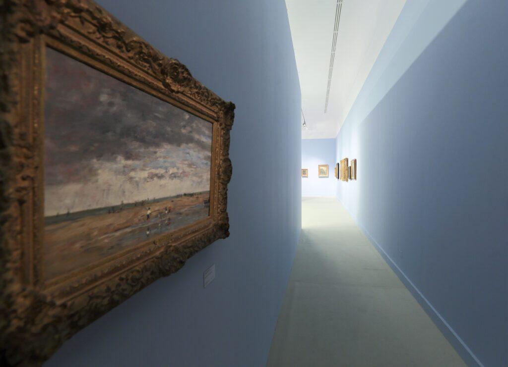 Fotografia przedstawia wąskie przejście prowadzące do głównej ekspozycji wystawy. Przejście przypomina wąski korytarz, w tle którego wyłania się rozświetlony widok wystawy. Ściany są błękitne, na podłodze leży dywanowa wykładzina w jasnym piaskowym kolorze. Na pierwszym planie, po lewej stronie, znajduje się obraz malowany impresyjnie miękkimi pociągnięcia pędzla, przedstawiający wędkarzy na brzegu morza. Obraz jest w rzeźbionej i złoconej ramie, oświetlony delikatnym punktowym światłem.