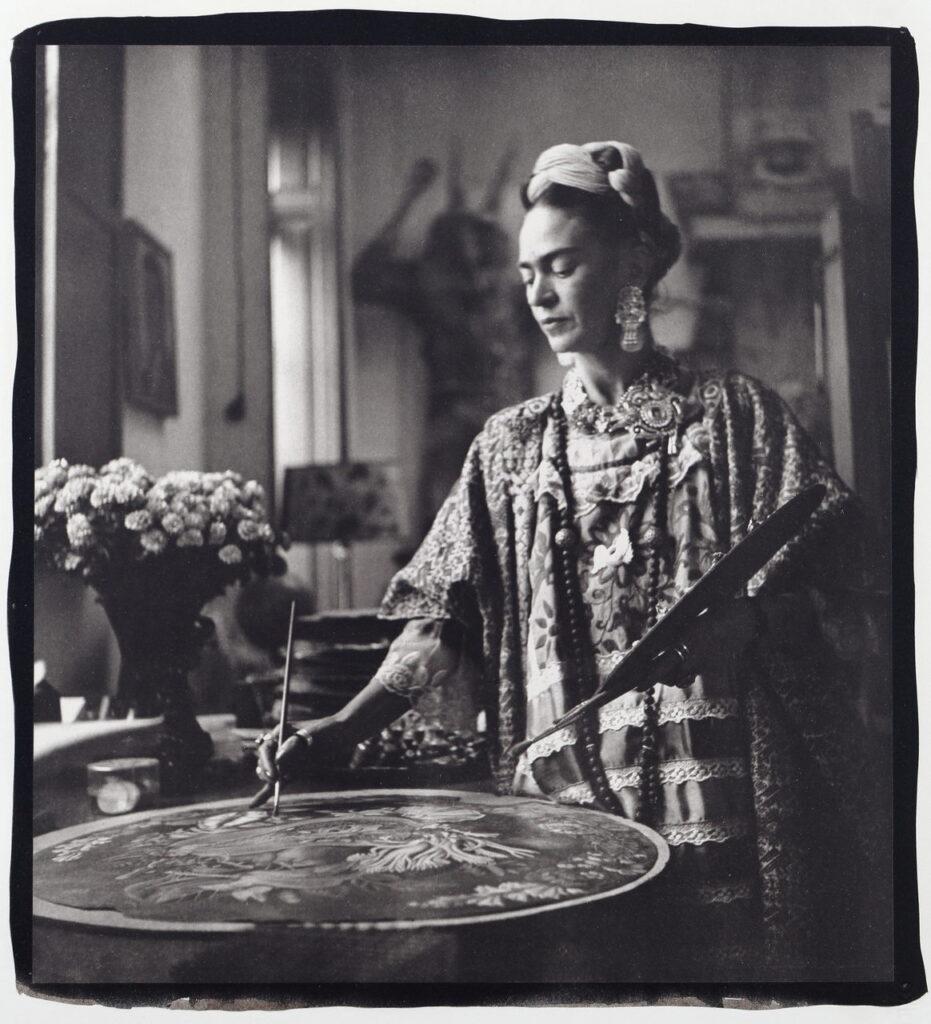 Czarno-biała fotografia przedstawia Fridę z profilu, ubraną w piękny bogato zdobiony strój. Maluje ona obraz trzymając pędzel w jednej ręce, a paletę malarską w drugiej. W tle widać nieostre wnętrze pracowni, które jest wypełnione kwiatami i obrazami.