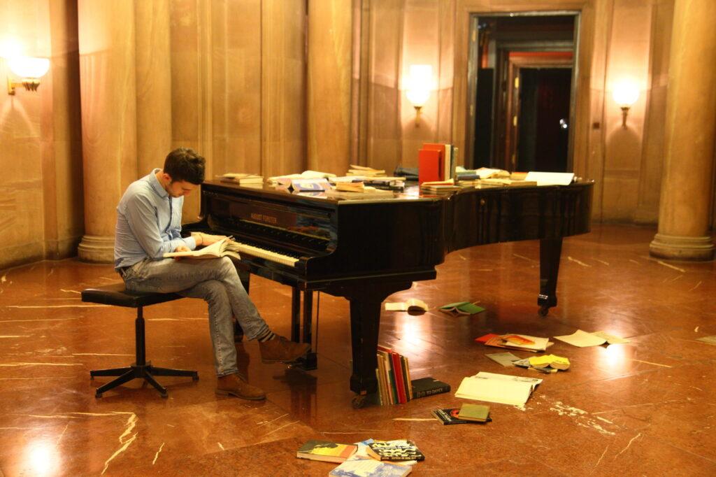 W centralnej części zdjęcia widzimy czarny fortepian, przy którym siedzi zaczytany, młody mężczyzna.  Na marmurowej podłodze oraz na instrumencie leżą książki. W tle dostrzegamy część architektury  holu zamkowego: kolumny i wejście do jednej z sal. Przestrzeń oświetlają 3 kinkiety.