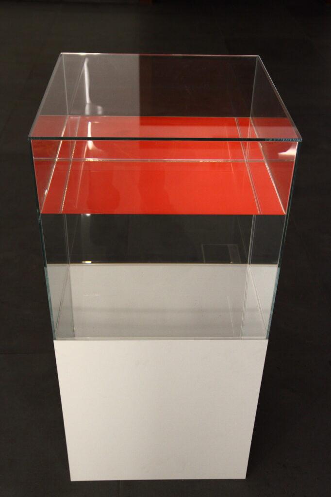 Zdjęcie przedstawia instalację świetlną składającą się z białego postumentu oraz stojącej na nim i  wypełnionej przezroczystym płynem szklanej gabloty, przywodzącej na myśl akwarium. Górna  warstwa płynnej substancji jest czerwona, prawdopodobnie jest to efekt złudzenia optycznego. Tło zdjęcia jest czarne.