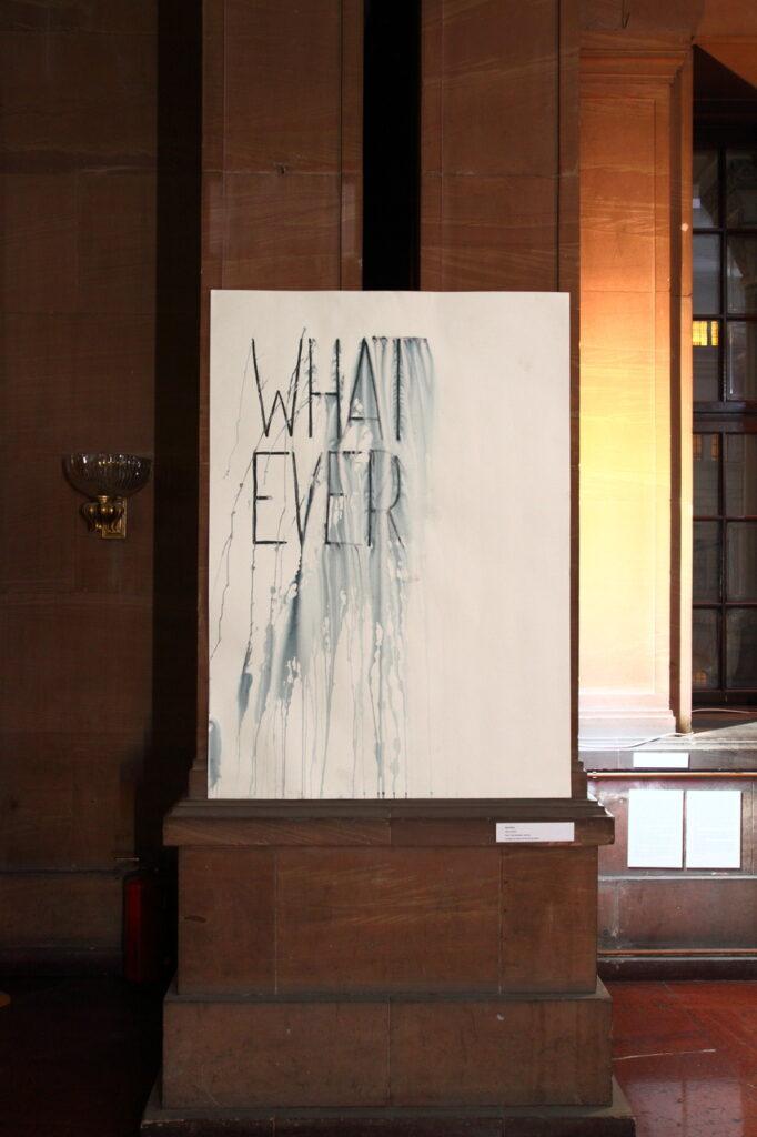 """Główny element zdjęcia stanowi nieco rozmyty, zachlapany farbą, ciemny napis w języku angielskim:  """"WHATEVER"""" (po polsku """"cokolwiek""""). Został on rozbity na dwa wersy i umieszczony na białym,  dużych rozmiarów papierze. Praca przymocowana jest do dwóch kolumn zamkowego holu. W tle widzimy fragment okna oraz kinkiet na ścianie."""