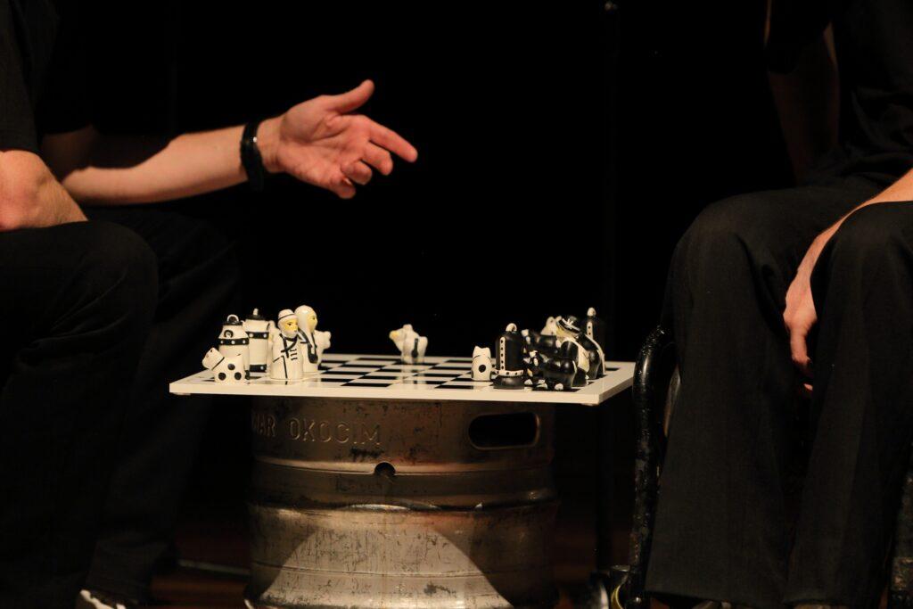 Głównym obiektem widzianym na fotografii jest ustawiona na metalowej beczce od piwa szachownica. Na jej biało-czarnych polach ustawione są figury. Ich forma wskazuje, że nie są to zwyczajne, standardowej wielkości szachy. Osoby rozgrywające partię nie są widoczne. O tym, że toczy się gra, świadczą jedynie wynurzające się z ciemności ręce. Aktor po lewej stronie wyciągnął prawą otwartą dłoń. Kieruje ją ku drugiej postaci, której rękę widzimy opuszczoną wzdłuż ciemnych spodni.