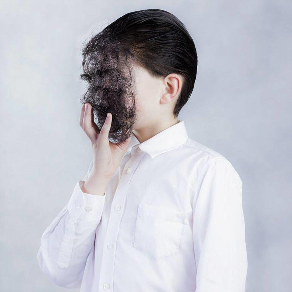 Na fotografii widać portret młodej osoby w białej, zapinanej na guziki koszuli z kołnierzykiem, trzymającej w dłoni maskę z włosów zakrywającą jej twarz. Postać ma krótkie, zaczesane do tyłu, ciemne włosy. Tło jest jasnoszare, jednolite.