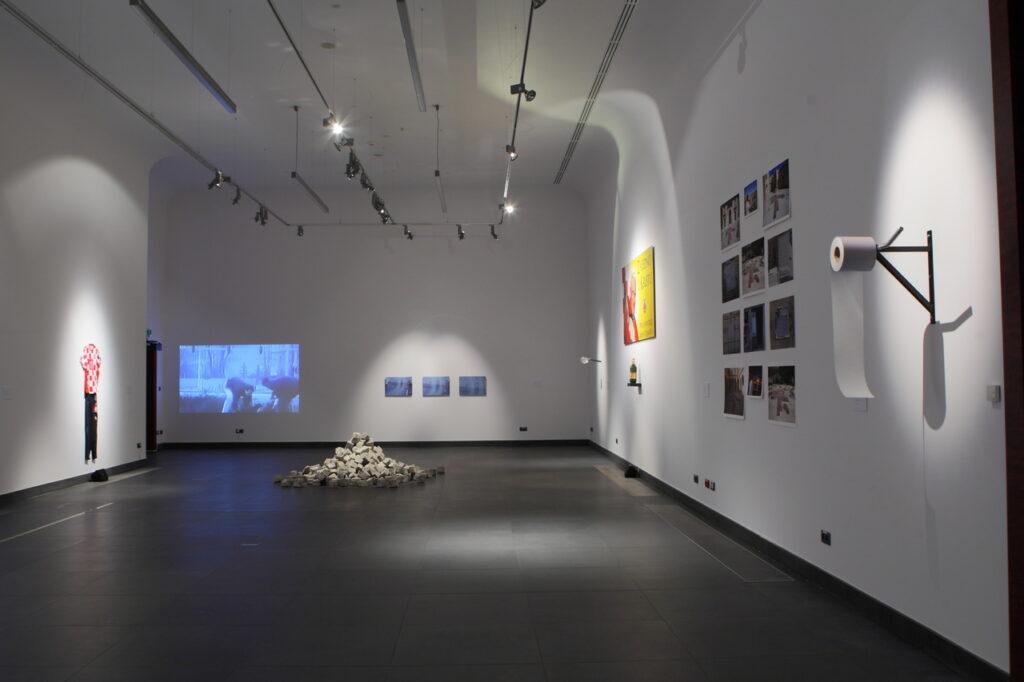 Na zdjęciu widzimy fragment aranżacji wystawy w Sali Wystaw. Na białych ścianach wiszą fotografie, instalacje, z tyłu wyświetlany jest obraz wideo, a na grafitowej podłodze znajduje się stos kostki brukowej. Pod sufitem zawieszone są reflektory oświetlające ekspozycję.