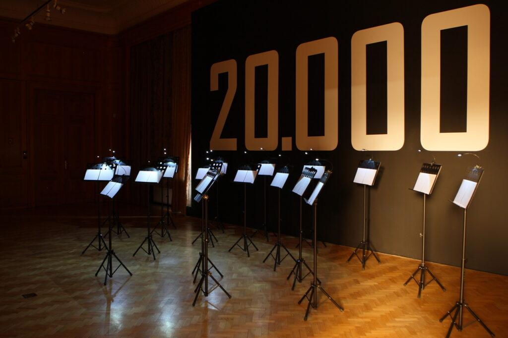 """Na zdjęciu widzimy podświetlone pulpity do nut stojące na drewnianej podłodze. Za nimi znajduje się czarna ściana z dużymi białymi cyframi """"20.000""""."""