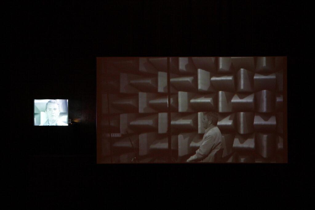 Na zdjęciu widzimy instalację wideo składająca się z dwóch filmów: jeden wyświetlany jest na małym ekranie po lewej, drugi zaś, po prawej, jest znacznie większą projekcją. Na zatrzymanych kadrach dostrzegamy tego samego mężczyznę, jakby oglądającego się w telewizorze. Tło zdjęcia jest czarne.