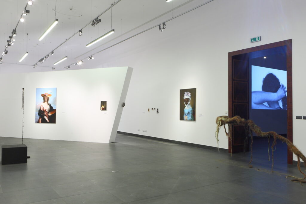 Zdjęcie przedstawia fragment aranżacji wystawy. Z lewej strony widzimy białą, wolnostojącą ściankę oraz białe ściany sali wystaw, na których powieszone są prace z wystawy. Z prawej strony zaś podwieszoną, tuż nad grafitową podłogą, instalację z włosów, przypominającą długi korzeń. Za nią znajduje się przejście do kolejnej Sali, gdzie wyświetlany jest czarno-biały film. Pod sufitem widać listwy oświetleniowe z lampami.