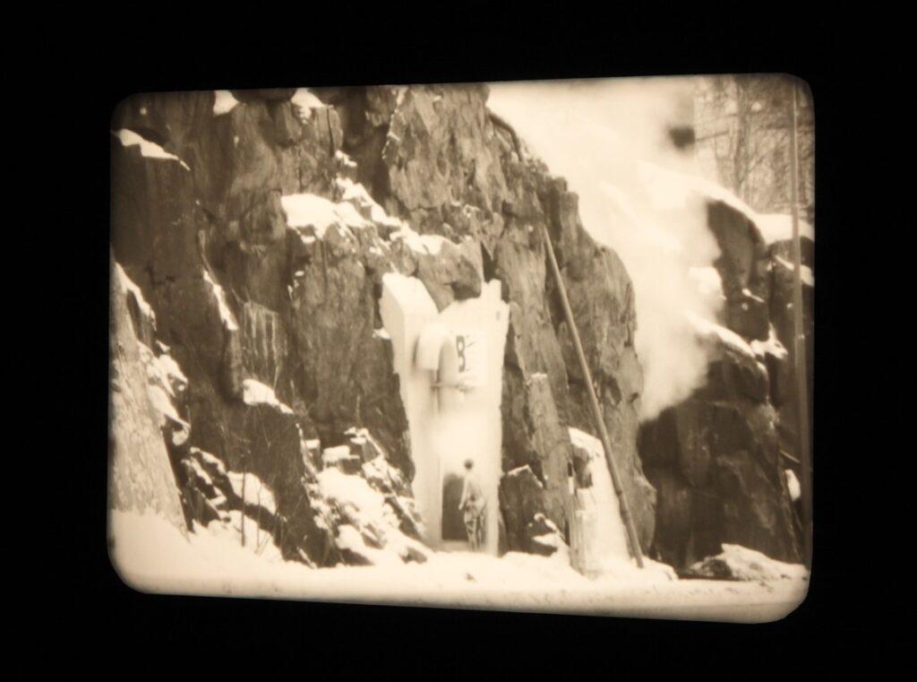 Na zdjęciu widzimy zatrzymany kadr z czarno-białego filmu. Przedstawia on fragment ściany skalnej pokrytej śniegiem oraz niewyraźną postać mężczyzny pośrodku. Z prawej strony kadru można dostrzec lawinę śnieżną.