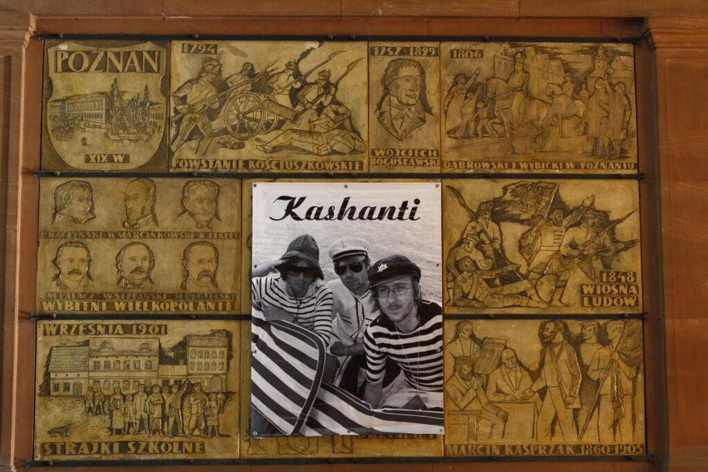 """Fotografia przedstawia fragment gipsowej płaskorzeźbionej płyty z zamkowego Holu Kolumnowego, przedstawiającej sceny z historii Poznania i Wielkopolski. Pyty te, znajdujące się do dziś na ścianach holu, wykonane zostały w 1966 roku w typowej dla socrealistycznych prac stylistyce i wydźwięku ideologicznym. Pośrodku płyty umieszczony jest czarno-biały plakat przypominający plakat zespołu muzycznego, który przedstawia trzech mężczyzn do pasa w górę, w marynarskich strojach w pasy na tle wody. Nad nimi znajduje się napis """"Kashanti""""."""