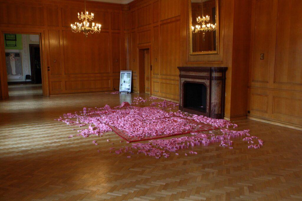 """Fotografia przedstawia zamkowy Pokój Brzozowy, nazwa pokoju pochodzi od boazerii wykonanej z drewna brzozowego w kolorze jasnego brązu, pokrywającej wszystkie ściany pomieszczenia. Na pierwszym planie widoczny jest, znajdujący się centrum pokoju, duży czerwony dywan, na którym rozsypane zostało kilkaset różowych pudełek zapałek ze złotym napisem """"ART"""". Dywan leży przed dużym kamiennym kominkiem, nad którym wisi ogromne lustro w złotej ramie. W lustrze odbija się rozświetlony kandelabrowy żyrandol zwisający w tle z sufitu i oświetlający całe wnętrze. W narożniku pokoju stoi pionowo na ziemi monitor telewizora wyświetlający film. Aranżacja wnętrza jest elegancka i przywołuje skojarzenia z pałacowym salonem."""