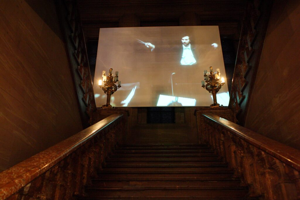 Fotografia przedstawia, w ujęciu od dołu, zamkowe Schody Paradne wykonane z czerwonego marmuru. Kamienne poręcze wieńczą u góry dwa złote kandelabry. Sfotografowana przestrzeń jest zaciemniona i nastrojowa. U góry schodów, w tle fotografii, perspektywę zamyka ogromnych rozmiarów ekran, na którym wyświetlane są zbliżenia na postać dyrygenta z uniesionymi rękami i batutą trzymanej w prawej dłoni, który dyryguje orkiestrą.