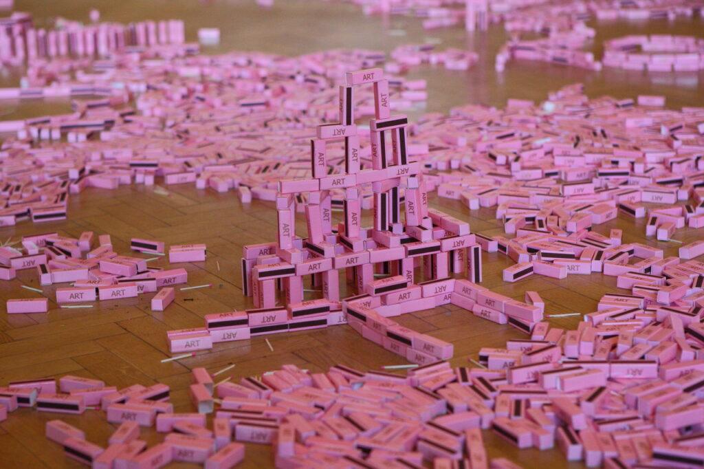 """Na zdjęciu widzimy instalację artystyczną, która powstała z rozrzuconych na drewnianej podłodze różowych pudełek od zapałek z napisem: """"ART"""". Część pudełek zwiedzający wystawę ułożyli w wieżę lub napisy."""
