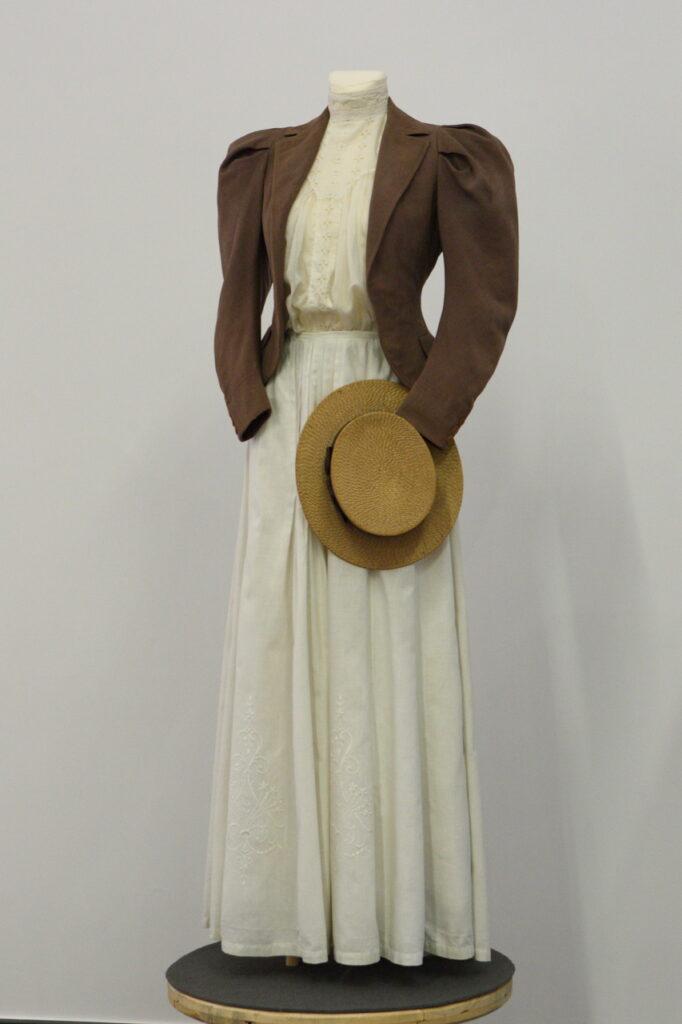 Na zdjęciu, w centralnej jego części, widzimy damskiego manekina ubranego w długą, białą suknię oraz brązowy żakiet. Przy rękawie żakietu przyczepiony jest słomkowy kapelusz. Tło jest białe.