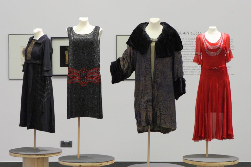 Na zdjęciu widzimy cztery damskie manekiny. Pierwszy, z lewej, ubrany jest w ciemną, długą suknię przypominająca płaszcz, drugi w czarną suknię bez rękawów wykonaną z połyskliwego materiału, trzeci w ciężki płaszcz z dużym, futrzanym kołnierzem, a ostatni manekin ubrany jest w elegancką, czerwoną wieczorową suknię, uszytą z przeźroczystej tkaniny. W tle widzimy trzy obrazy oraz tekst umieszczony na ścianie, są one jednak nieczytelne i przesłonięte manekinami.